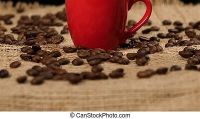 Coffee beans falling into red small cup. Slow motion. Cam...