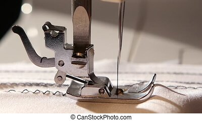 Sewing machine sews a zigzag stitch on white fabric. Slow...