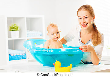 Happy family mother bathes the baby in  bath