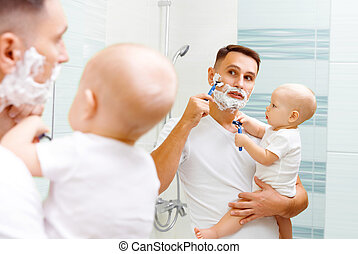Dad and baby son shave in the bathroom