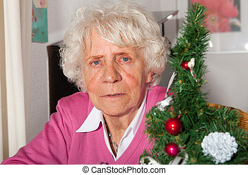 Old woman - Very old woman in sitting near a christmas tree