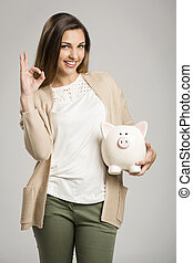 My savings - Beautiful and happy woman holding a piggy bank,...