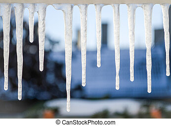 icicles hanging from windowsill - close-up picture of...