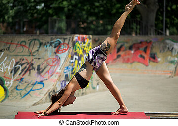 Young beautiful girl with nice body does yoga on the nature.