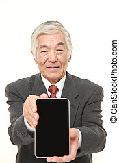 senior Japanese businessman holding a Tablet PC - studio...