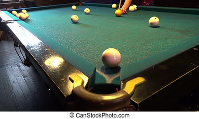 Young woman playing billiard - Pool game, the ball gets in...