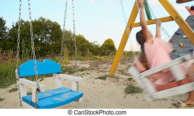 Mom pushes daughter on a swing