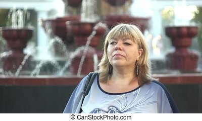 a woman stands by the fountain - Portrait of happy woman...