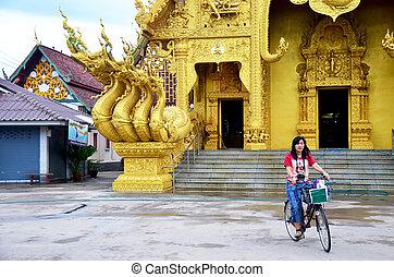 Traveler thai woman biking bicycle at front of Wat Sri Pan...