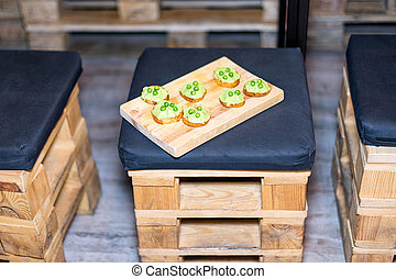 Wooden tray of appetizers on pallet coffee table at banquet.