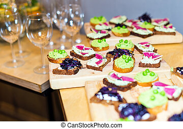 Wooden tray of vegetarian appetizers on pallet coffee table at banquet.