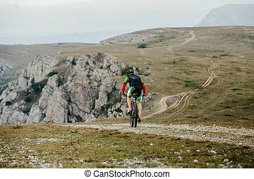 rider cyclists sports mountainbike rides on top of a...