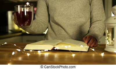 woman drinking red tea and reading book at night. blurred lights in background