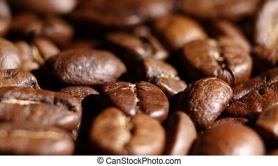 Pile of roasted coffee beans rotating. Close up
