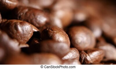 Big heap of fragrant roasted brown coffee beans. Rotating....