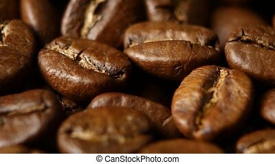 Roasted coffee beans on a table. Rotating. Close up -...