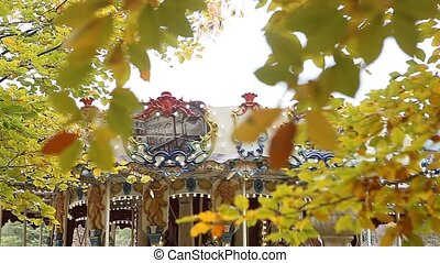 Yellow autumn leaves with merry-go-round in background -...