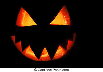 Pumpkin carved into spooky demon face for haloween,festival,...