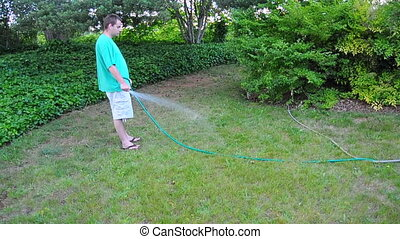 Man Waters the Grass Lawn Yard - A causal white male waters...