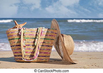 Women's hat and bag on the beach