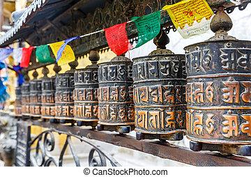 Prayer wheels and prayer flags - Close up photo of prayer...