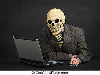 Terrible skeleton sits at black office with laptop - The...