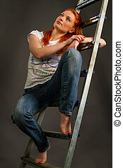 young red-haired girl leaning on a ladder
