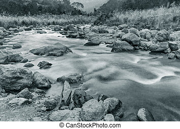 River water flowing through rocks at dawn, Sikkim, India -...