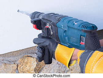 rock-dril - worker  with rock-drill warms the wall