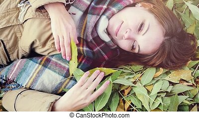 top view of autumn romantic woman lying over leaves and smiling in slowmotion. 1920x1080