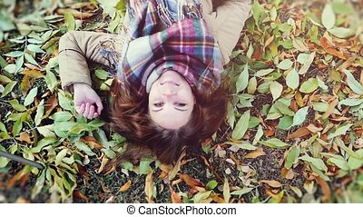 top view of autumn woman lying down over leaves and smiling...
