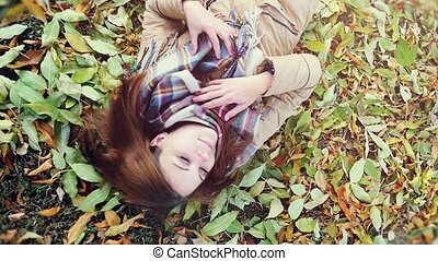 top view of autumn beautiful woman lying over leaves and smiling in slowmotion.