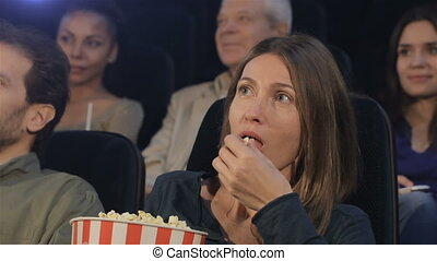 Woman puts popcorn into her mouth at the movie theater -...