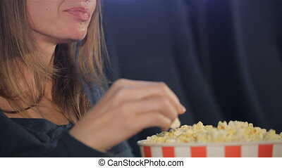 Woman takes flakes of popcorn from the bucket