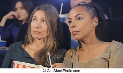 Two women looking at the screen at the movie theater. Middle...