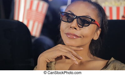 Woman in 3D glasses holds her hand near her chin at the movie theater