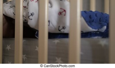 Cute baby feet from beneath a blanket between crib railings....