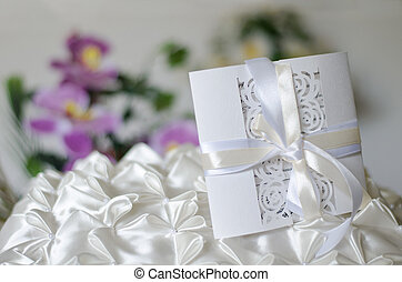 White wedding invitation on a satin pillow