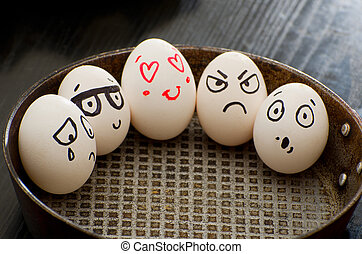 Whole eggs in a frying pan with different emotions