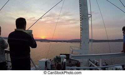 man photographs the sunset from the deck