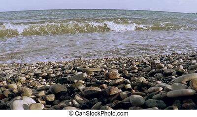 Stone tower on a seashore. - Seashore in background of sea...