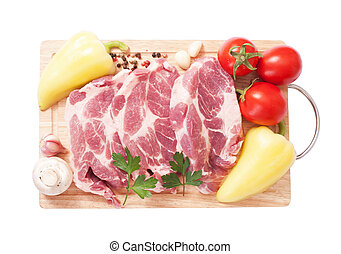meat. - Cooking meat. Pork with vegetables on wooden board....
