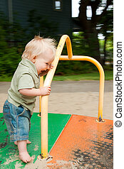 Children\'s Merry-Go-Round - A young boy plays on a merry go...