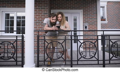 Married couple at doors of the house in the city. They watch...