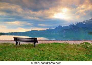 Empty bench at spring montain lake. Coast with mountains at horizon and in water mirror. Vintage toned photo.