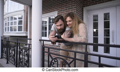 Young couple having bent to a handrail near the house.They...