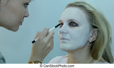 Professional make-up artist, using makeup to create a mask on Halloween