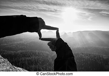 Female hands do frame gesture. Deep misty valley bellow sandsotne cliff.  Sunny spring daybreak