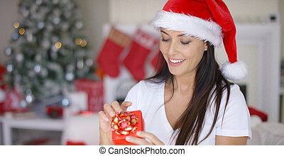 Smiling woman unwrapping her Christmas gift with a look of...