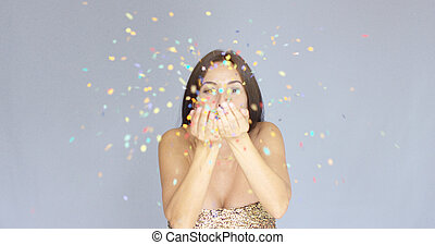 Young woman blowing colorful New Year confetti off the palms...